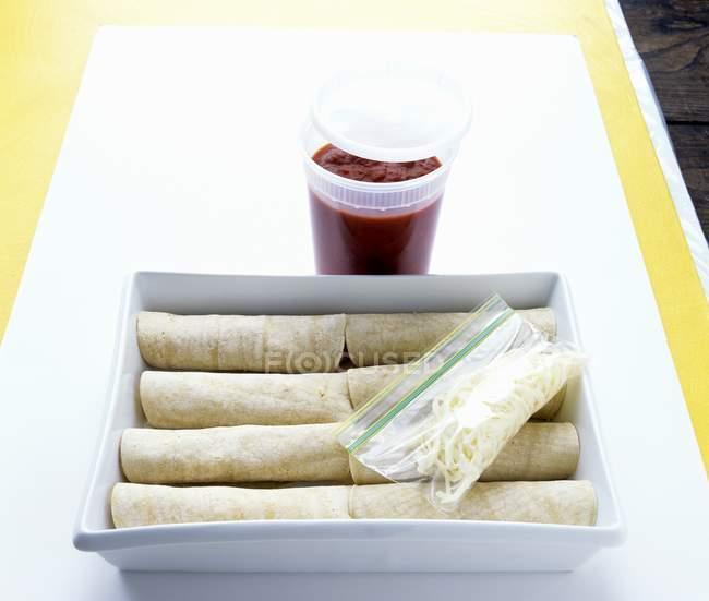 Vista elevada de Enchiladas rellenos en una cazuela con la salsa y los tallarines verduras - foto de stock