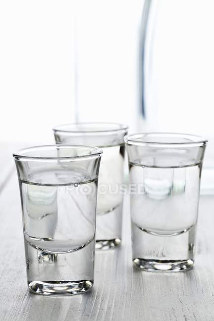 Closeup view of three glasses of Ouzo with carafe of water — Stock Photo