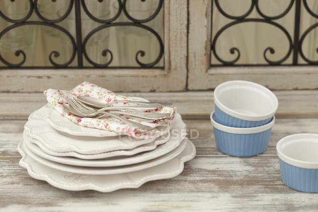 Tack of plates, a floral cloth — Stock Photo