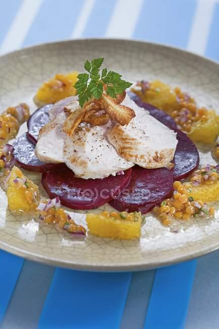 Pollo ruspante su barbabietola con una vinaigrette di lenticchie e arancione sul piatto sopra la superficie blu — Foto stock