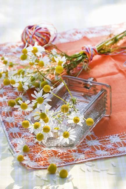 Flores de manzanilla con hilo de colores en un mantel naranja - foto de stock