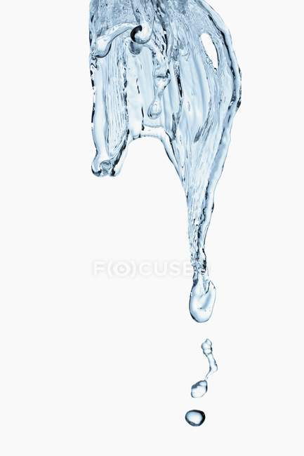 Closeup view of water flow and drops on white background — Stock Photo