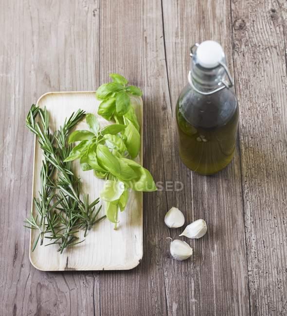 Базилик, розмарин и чеснок - ингредиенты для вливания оливкового масла на деревянную поверхность с бутылкой — стоковое фото