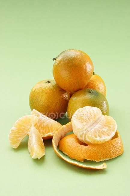 Целые и очищенные мандарины — стоковое фото
