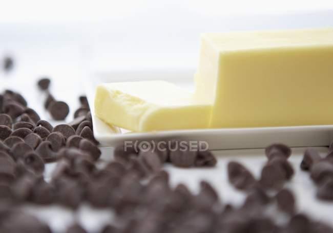 Vue de pépites de chocolat et le beurre coupé sur la plaque — Photo de stock