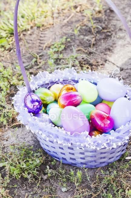 Vista elevada de uma cesta de Páscoa no chão com uma variedade de ovos decorativos — Fotografia de Stock