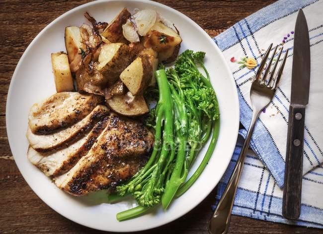 Frango grelhado fatiado, broccolini e batatas assadas com tomilho em uma placa branca em uma mesa de madeira com um guardanapo de xadrez azul — Fotografia de Stock
