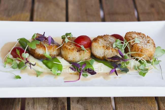 Capesante in piatto bianco sul tavolo del ristorante in piatto bianco — Foto stock