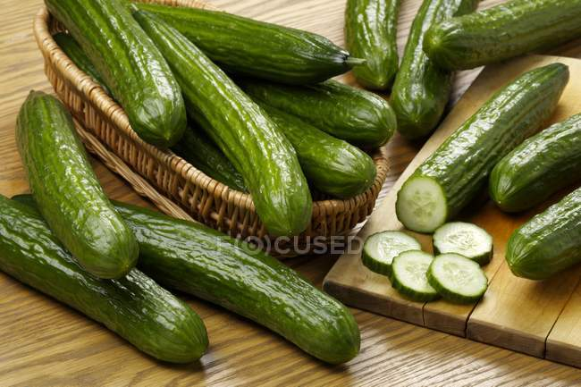 Fresh cucumbers with basket — Stock Photo