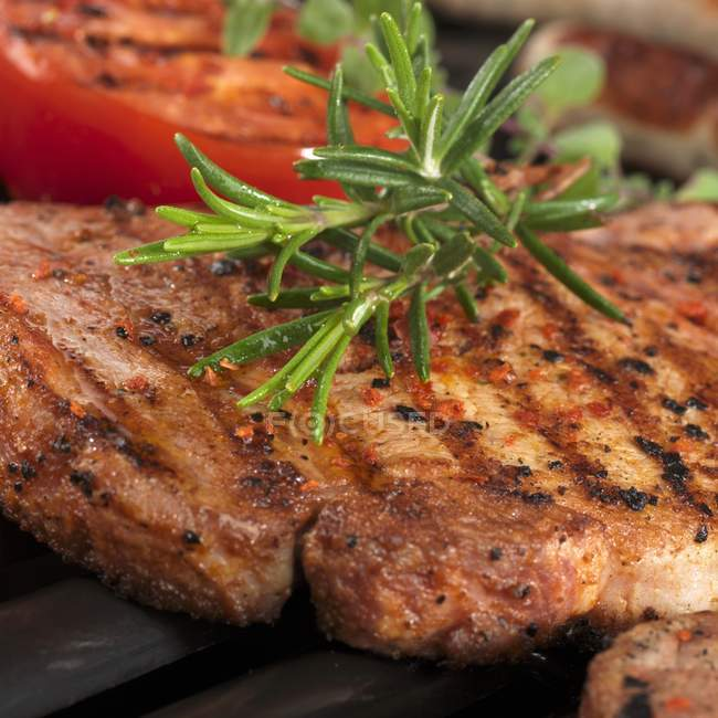 Grilled pork steak with fresh rosemary — Stock Photo