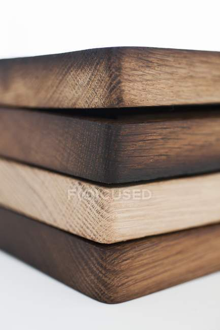 Closeup view of four stacked wooden chopping boards — Stock Photo