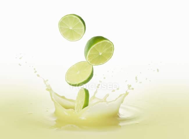 Лайми впадаючи соку лайма — стокове фото