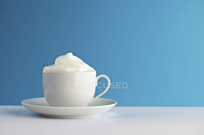 Closeup view of milk froth in white cup — Stock Photo