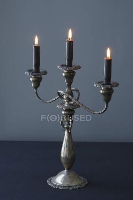 Vista del primo piano di un candelabro con tre candele accese scure — Foto stock