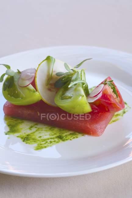 Fette di pomodoro verde e rosso sull'anguria — Foto stock