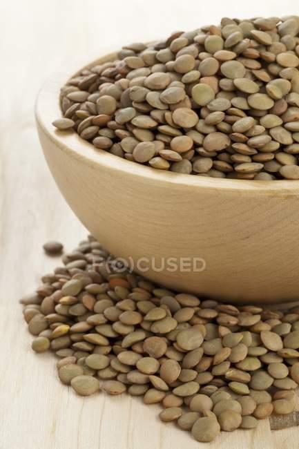 Vista del primo piano di lenticchie secche verde in una ciotola di legno — Foto stock