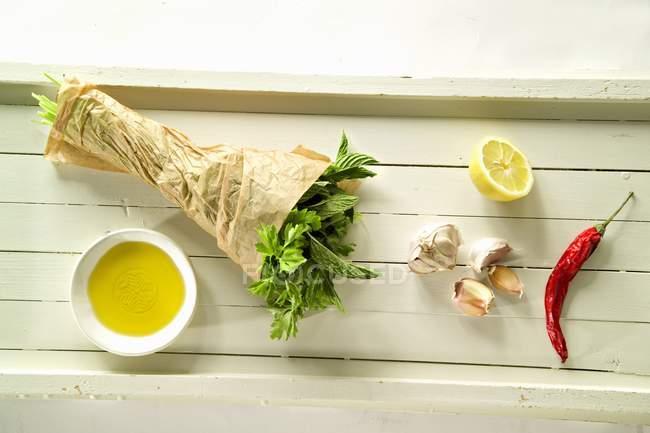Erbe, olio di peperoncino, aglio, limone e ulivi su superficie di legno — Foto stock