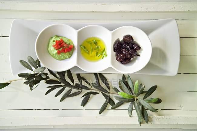 Tahini verdi, olio di oliva e olive nere in ciotole su superficie di legno — Foto stock