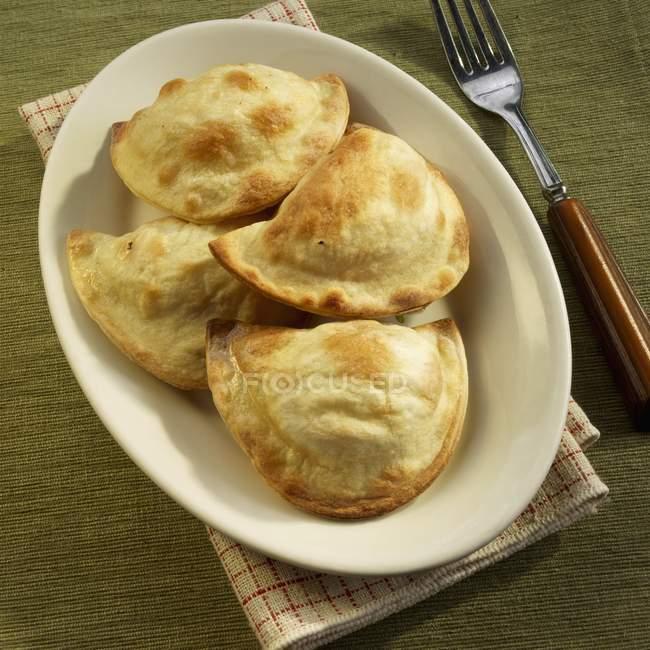 Quattro Pierogi ripieni di patate e pancetta affumicata sulla zolla bianca sopra asciugamano con forcella — Foto stock