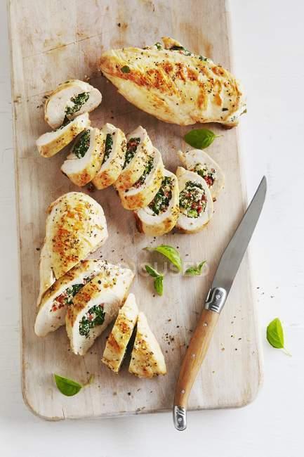 Vista elevata a fette di petto di pollo con ripieno di basilico — Foto stock