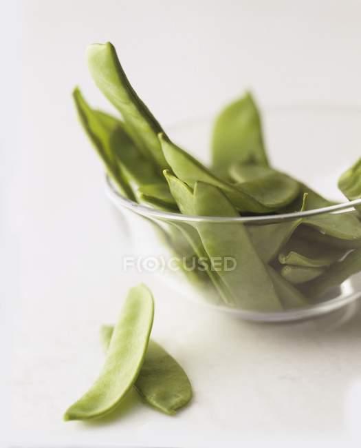 Fresco mange tout in una ciotola di vetro su priorità bassa bianca — Foto stock