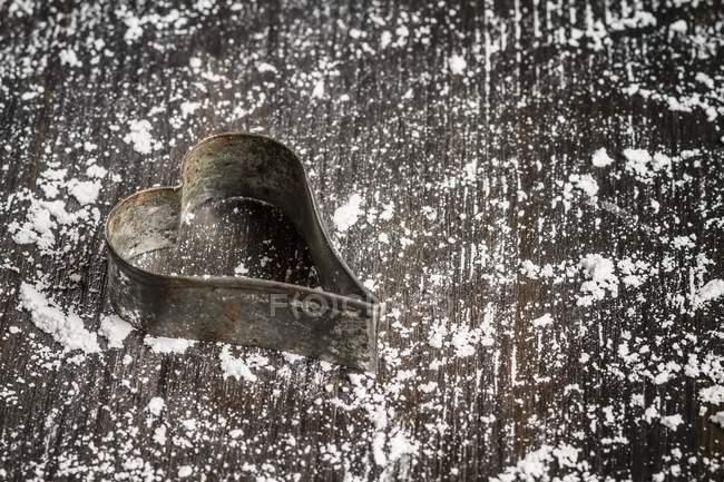 Primo piano vista di vecchia taglierina del biscotto a forma di cuore con farina su superficie di legno — Foto stock