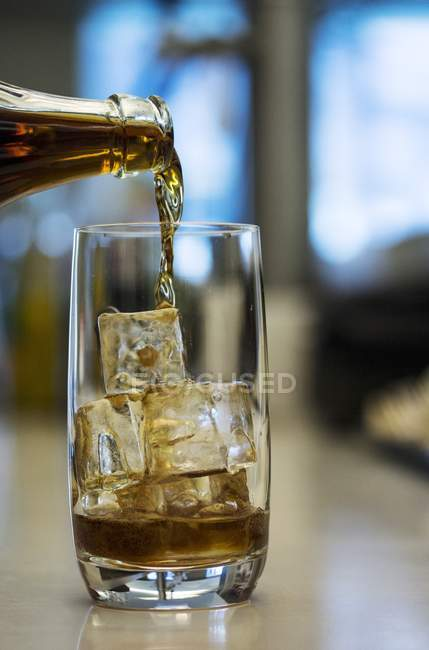Closeup view of Cola pouring to glass with ice cubes — Stock Photo