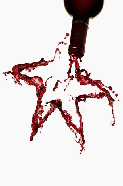 Red wine forming star shape — Stock Photo