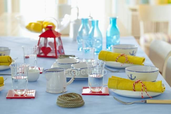 Una tavola imbandita con acqua e decorazioni marittime — Foto stock