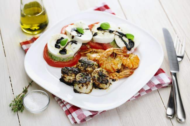 Jakobsmuscheln mit Garnelen und Caprese-Salat — Stockfoto