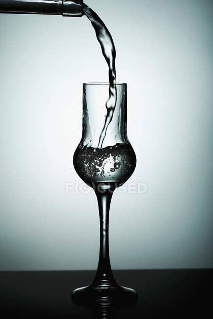 Closeup view of pouring transparent drink to glass — Stock Photo