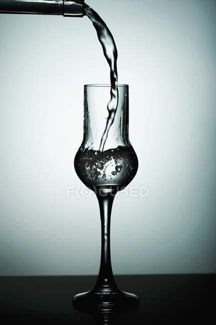 Detailansicht des strömenden transparent Getränk, Glas — Stockfoto