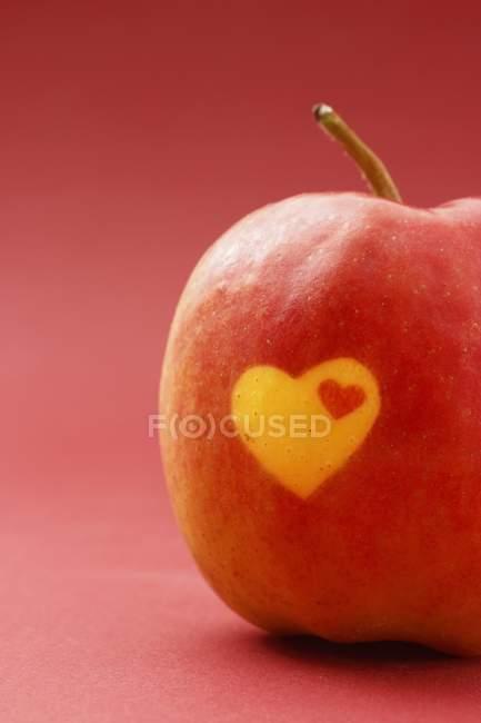 Крупный план красного яблока с сердцами на коже — стоковое фото