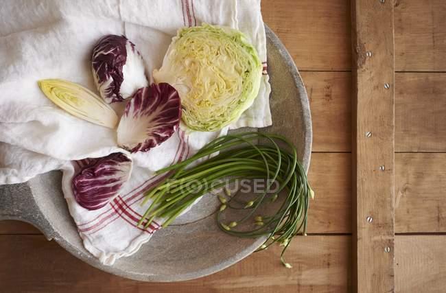 Асорті зелень, в тому числі, радіккіо, салат, цибуля, цикорій на плиті над деревної поверхні — стокове фото