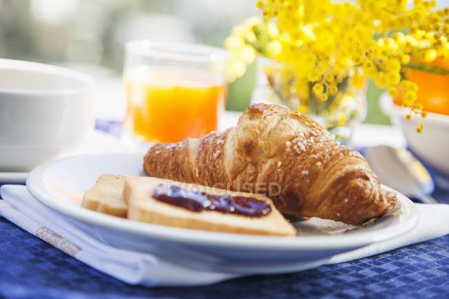 Breakfast of croissant on plate — Stock Photo