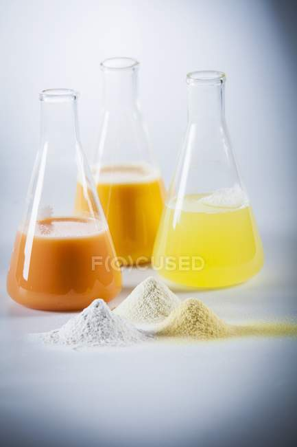 Still life with egg yolk, egg white and mixed egg in laboratory flasks and as powders — Stock Photo
