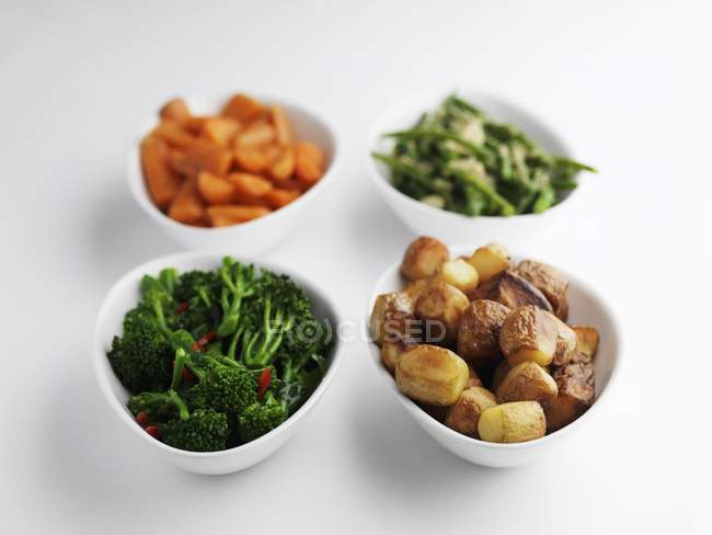 Side dishes of steamed vegetables and roast potatoes in bowls on white surface — Stock Photo