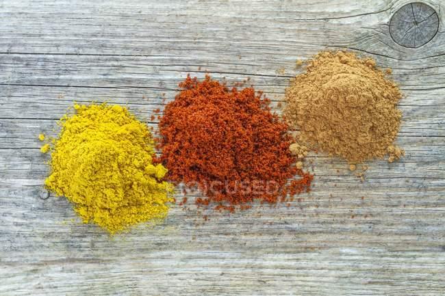 Vista superiore di tre mucchi di spezie differenti su superficie di legno — Foto stock