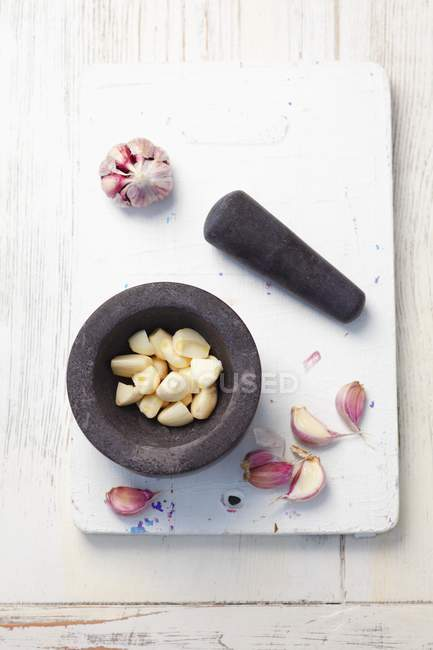 Dientes de ajo en mortero - foto de stock