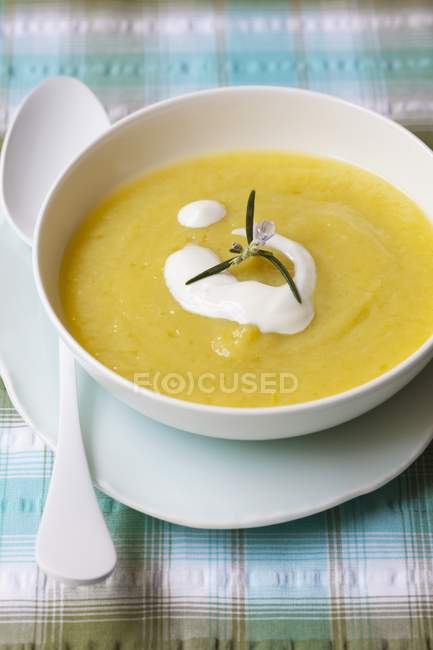 Creme von Zucchini Suppe garniert mit saurer Sahne in der Schüssel weiß über Platte mit Löffel — Stockfoto