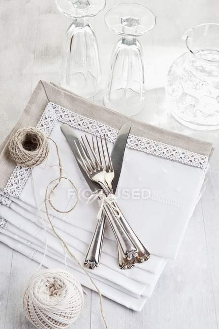 Elevated view of tied forks and knives with strings, towels and glasses on a white surface — Stock Photo