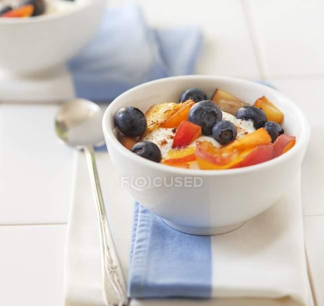 Yogur con muesli, duraznos y arándanos - foto de stock