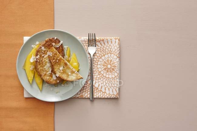 Vue de dessus des toasts Français avec copeaux de noix de coco et de mangue — Photo de stock