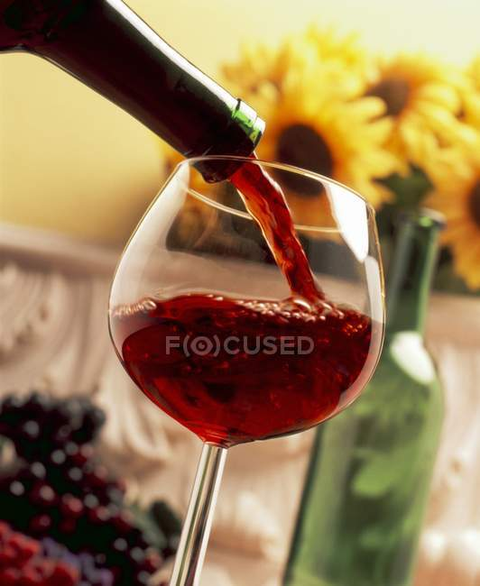Red wine being poured into glass — Stock Photo