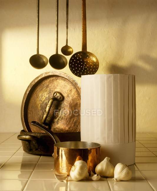 A chef hat, copper pots, ladles and garlic — Stock Photo