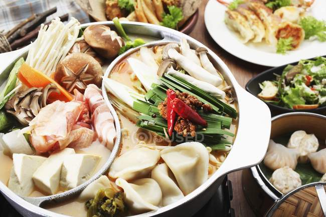 Chinese hotpot on wooden surface — Stock Photo