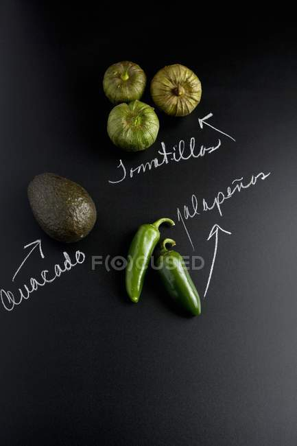 An avocado, jalapeos and tomatillos on a slate surface with labels — Stock Photo