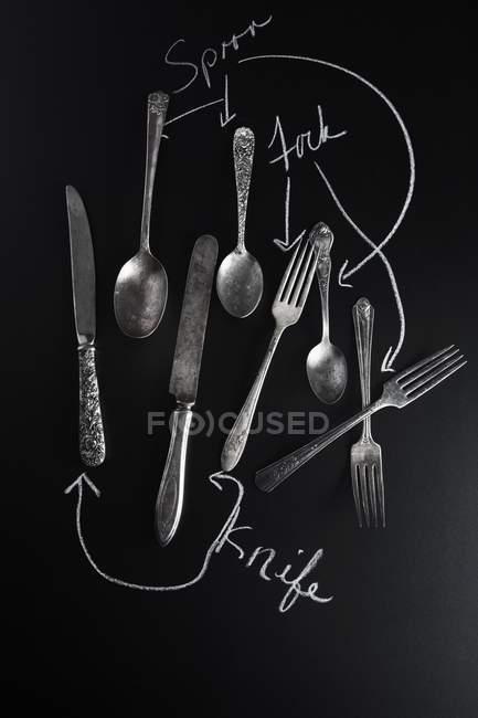 Vista superior de cuchillos, cucharas y tenedores en una superficie de pizarra con etiquetas - foto de stock