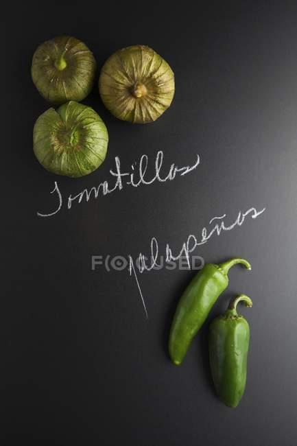 Tomatillos e jalapeos em uma superfície de ardósia preta com etiquetas — Fotografia de Stock