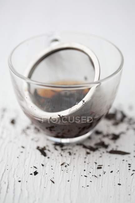 Tea strainer with black tea — Stock Photo
